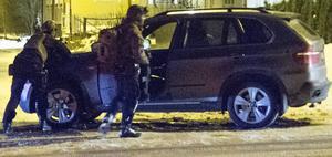 Poliserna från insatsstyrkan tog betäckning bakom bilarna.