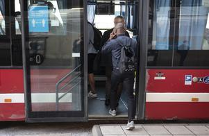 Passagerare kliver på bussen, där skyltningen på bussdörrarna uppmanar om att hålla avstånd. Foto: Naina Helén Jåma/TT