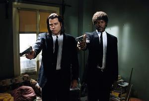 Hejdukarna Vincent Vega (John Travolta) och Jules Winnfield (Samuel L. Jackson) bär begravningskostym när de jobbar. Foto: Svensk Filmindustri