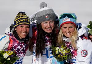 Justyna Kowalczyk, i mitten, på prispallen med Charlotte Kalla och Therese Johaug.