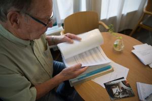 Palle Björkman visar stolt upp gamla dokument och bilder som varit till hjälp under restaureringen.