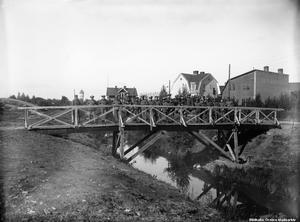 Här ser vi militärer på en gångbro över Lillån. Platsen är längs med Strandvägen i bostadsområdet Rynninge. Som synes fanns där inte lika många hus år 1919 som det gör idag. Foto: Örebro stadsarkiv