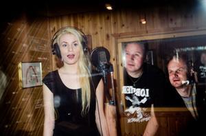 Hasse Spennare och P-O Larsson håller koll på Frida Zetterman när hon sjunger in sin sång i studion.