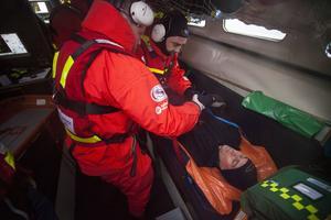 En av de skadade besättningsmännen säkras i båten på väg in till land.