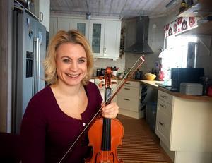 Jenny Elfving, violinist från Falun hemma i föräldrahemmets kök. På lördag spelar hon Mozart på Kristinehallen – men oftast hittar man henne i Céline Dions orkester i Las Vegas.