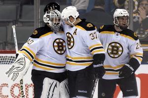 Bostonspelaren Patrice Bergeron klappar om målvakten. Till höger Daniel Paille. Bilden är tagen i november 2011. Ett halvår tidigare hade de vunnit Stanley Cup tillsammans. Foto: AP Photo