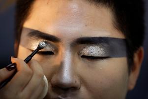 En makeupartist lägger glitter på en av artisternas ögon. Bild: TT.