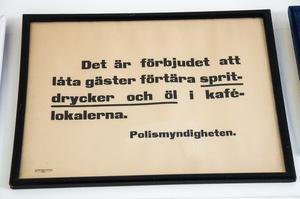 I köket har Ronny gjort en tavelvägg med diverse reklamskyltar och annat gammalt roligt, som den här skylten från Polismyndigheten.