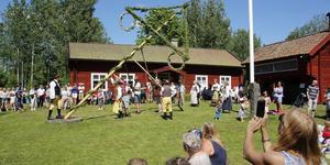 Med gemensamma krafter restes midsommarstången vid Möklinta hembygdsgård.