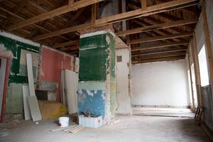 Från början var huset två butikslokaler med varsin ingång. Ytan i det här rummet, där skiljeväggen numer är riven, är 58 kvadratmeter. Bakom väggen till vänster i bild fanns soprum och urinoar i de ursprungliga ritningarna.