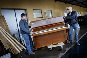 Pålastning. German Diaz från Chile (t v) lyfter ett av de sista pianona som ska med på containerlasset till Santiago. T h medhjälparen Jonathan Smith.