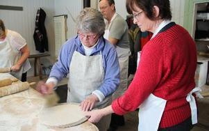 Britt-Marie Nordh och Sonja Nilsson jobbade i takt med att kavla och sedan lägga kakorn a på de nytillverkade brödspadarna för att sedan bäras till bakugnen. FOTO: KERSTIN ERIKSSON