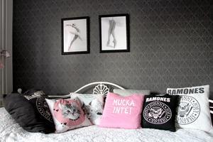 Tuffa kuddar av t-shirtar och balettdansöser på väggen i Iggys rum.