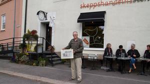 Jan-Erik Hedberg hållandes en tavla av den gamla skeppshandeln, så som den såg ut i början av 1900-talet utanför nuvarande kafé.