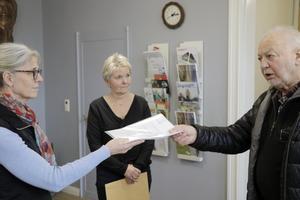 Här lämnar Cur-Eric Hermansson över namnlistor och skrivelser till kommundirektören Isabell Landström. I bakgrunden oppositionsrådet Pia-Maria Johansson (LPO).