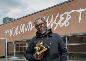 Sverigeaktuella Arthur Jafa med guldlejonet som han belönades med på årets Venedigbiennal. Pressbild. Foto: Albin Dahlström/Moderna Museet