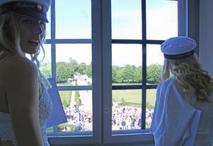 Fönstertittare. Rebecca Båvenäs och Elvira Ekberg kikar ut genom fönstret för att hitta var just deras familj står där utanför.