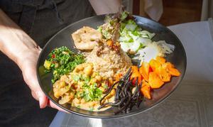 Förslag på vegansk lunch som bland annat innehåller kikärtsröra, olika kålsorter exempelvis stekt savoykål, direkt från egna landet, alger och sjögräs. Det finns också ett fiskalternativ.