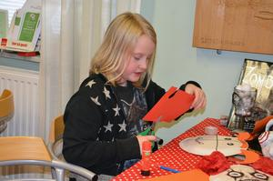 Tindra Wallin Persson klipper ut horn i orange papp till sin mask.