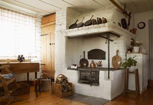 Foto: Mattias Bardå En vacker vedspis är ett lockande inslag i köket. Bilden är ur boken