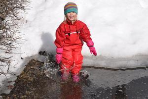 Wilma njuter av att hoppa i vattenpölarna som framkommit av det härliga vårvädret.