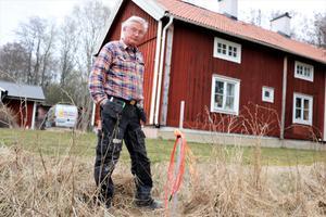 Olli Lehikoinen vid den orangea fiberslangen i Ormesta som väntar på att bli inkopplad i huset sex meter bort.