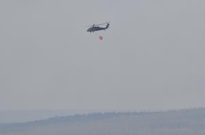 En militärhelikopter, Black Hawk, återvänder i röken till Särna, när insatsen på den östra flanken avbröts.