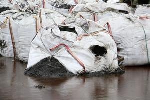 En del av säckarna är trasiga och innehållet har läckt ut på marken.
