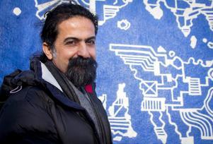 Seywan Saeedian vid muralmålningen av en subjektiv världskarta på Konstcentrums yttervägg.