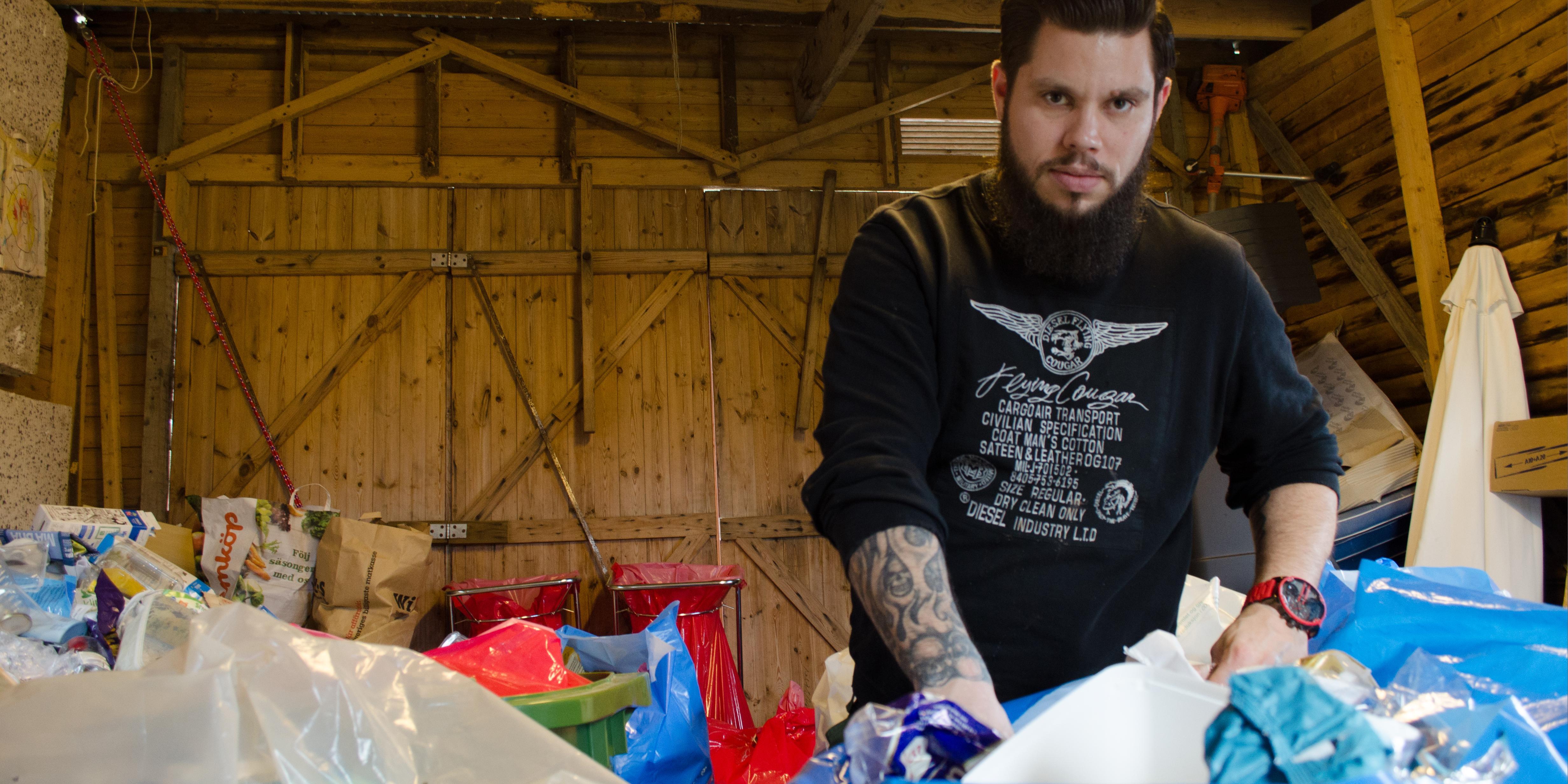 I garaget hemma vid huset i Karlsbyheden står David Andersson och sorterar förpackningar.