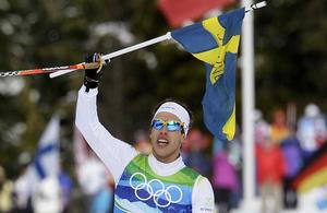 Hjältekvartett. Marcus Hellner - en av dagens fyra svenska OS-hjältar - hade tid att ta emot en flagga under sin defilering in i mål. FOTO: SCANPIX