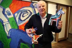 Curt Aspelin visar den nya moderna versionen av dalahäst designad Bengt Lindström.