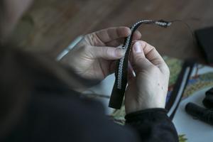 Flätan sys fast mot läderbandet med den osynliga nylontråden.