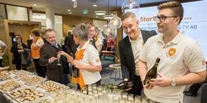 Arbogakontorets chef Ralph Pihlqvist häller upp bubbel och hälsar gästerna välkomna till nyinvigningen av Sparbanken. Cathrine Folkesson och Freddie Rosander är också personal som hjälper till.