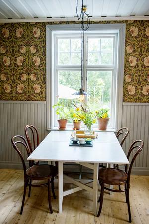 Köket har en ombonad känsla med gråmålad pärlspont och fönsterfoder. Tapeten