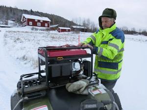 John Westerlund i Börjesjö kör fyrhjuling i strömlöst land, på väg med reservaggregat till en granne. De hjälps åt att hålla frysarna i gång.