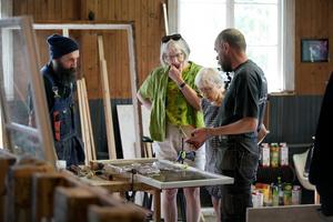 Stefan Sjödahl och Stefan Andersson visar besökarna Margreth Larsson och Hannelore Björklund hur man renoverar fönster.