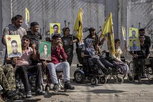 Kurdiska soldater som skadats i kriget mot IS demonstrerar utanför FN-byggnaden i Qamishli med plakat på stupade kamrater. Foto: AP Photo