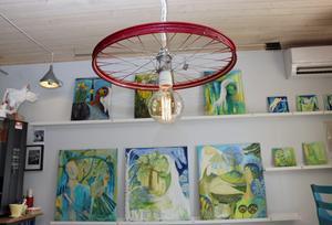 Här är ett obegagnat cykelhjul som såldes  i anrika cykelbutiken Forsmans. Hänger nu i taket med en lampa. Vid väggen syns galleriet som den här månaden pryds  med tavlor av Annette Segerberg från Torsåker.