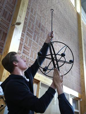 Erik Engvall hjälper till att hänga upp en av de cirka 50 ljusstakarna.