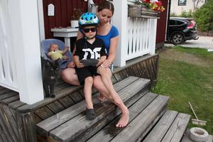 Emma Ruuska plåstrar om Wilmer, 4 år, som cyklat omkull på gatan och slagit knät. Lillebror Noel, sju veckor, tittar på.