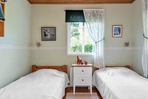 Ljust sovrum med fönster i två väderstreck. Ljusgrön tapet med mönstrad bård samt trägolv. Foto: Fisheye Foto