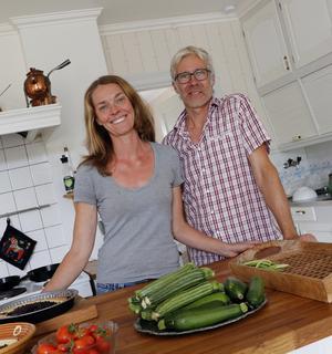 Sareidah Hildebrand och Joakim Lundström i det stora lantliga köket, med en del av dagens skörd av grönsaker.