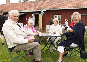 Åke och Rut Rudolfsson, längst fram i bild, har hjälpt till med årets festligheter. Under dagen kunde de avnjuta laxstut från serveringen. Bakom i bild sitter Ingrid Bergvall och Eva Söder.
