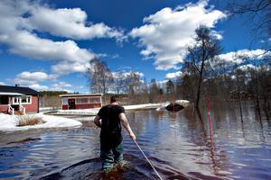 Ilkka har tagit på sig vadarstövlarna och drar båten med reporter och Lena i. Vattnet går upp till låren som högst.