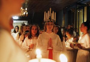 Lucia Emma Sving skred uppför mittgången till kyrkan, flankerad av deltagare från Hudikgympan.