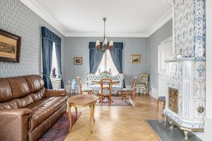 Vardagsrum med kakelugn med tapetserade väggar och parkettgolv. Foto: Erik Olsson Fastighetsförmedling