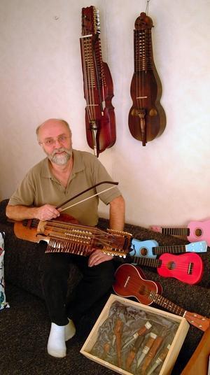 Allan Lundqvist med tre av sina egenhändigt byggda nyckelharpor och några av sina ukulelegitarrer.
