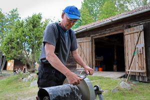 Stig-Åke Svensson håller på att slipa en lie. Han var med och startade upp Källslättenföreningen 1966. Att han skulle hålla på hela livet var det ingen som trodde, säger Stig-Åke.