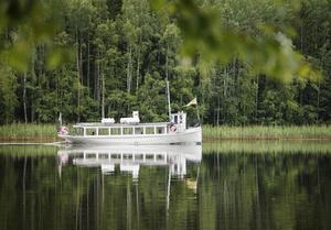 Båten Emma passerar tyst förbi och förstärker idyllen.